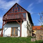 Hütte Helgas Gartenseite: sichtbar ist ein Fachwerkhaus mit großem Panoramafenster und Balkon, blauer Himmel und Garten